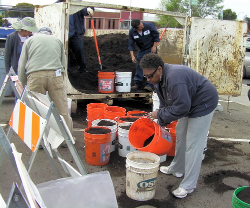 Compost is poured into a bucket for a resident to take home at the Earth Day compost event at Richmond Civic Center Plaza on Saturday.