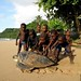 children playing with a green sea turtle on the beach in Príncipe Island. (Sao Tomé & Príncipe Islands)