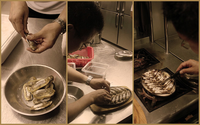 The chef cuts the clams, arranges them on a hotplate and cooks them there