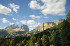 The Dolomites in Italy viewed from the road (Vee living life to the full) Tags: italy leger travel touring holiday landscape rock pass pordoi sella towers mountain people nikond300 heathaze valley sky clouds sunshine trees