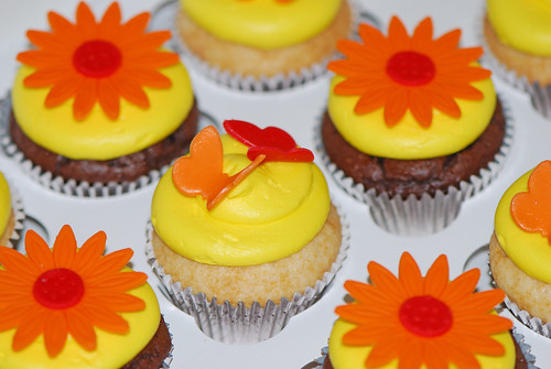 yellow orange and red cupcakes topped with butterflies and daisies