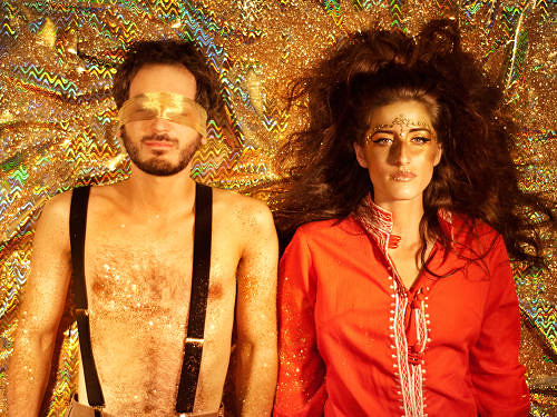 a man and a woman lie next to each other on a gold, sparkly background. the man has his eyes blindfolded with a gold piece of the cloth. the woman has her eyes open. she has a golden bronze shimmer on her face.