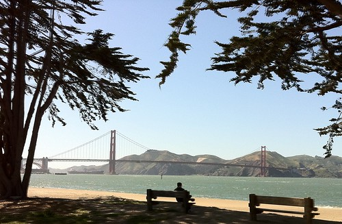 man on bench facing Golden Gate