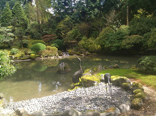 Bronze sculpture of herons and a live mallard duck at a pond in the Japanese Garden