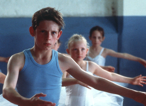 Billy Elliot, a white boy in a blue tank top, in a ballet class