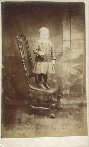 Portrait of a young boy standing on a chair by H. Thomas (1860s)