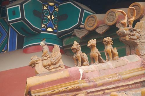 An einer Giebelecke ist ein Figur, die auf einem Drachen reitet, gefolgt von drei lwenhnlichen Figuren