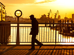 One Day, Hafencity - Hamburg (adde adesokan) Tags: street old shadow sun man water silhouette pen fence river walking 50mm harbour crane hamburg streetphotography olympus mann hafen sonne schatten
