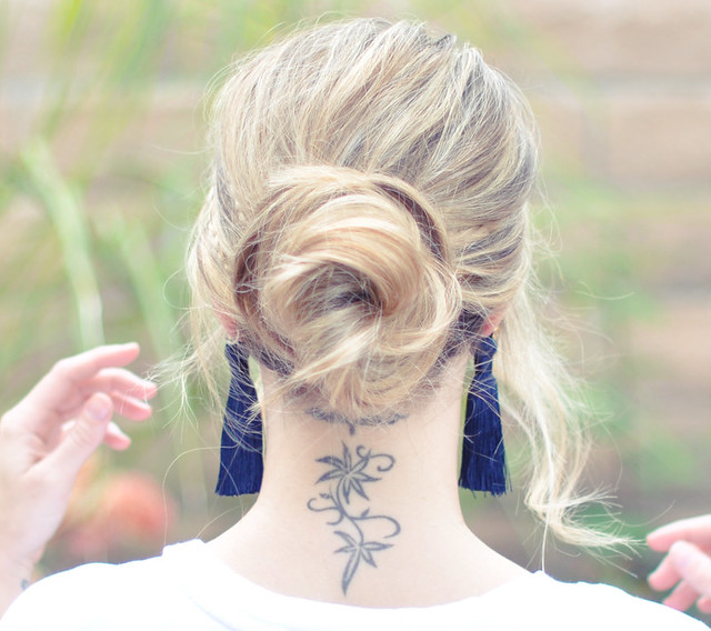 messy low bun and tassel earring and neck tattoo