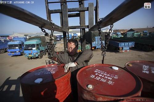 3月27日,河北省沧州泊头货场,郭伟明爬到车上装货。这次装了120个化工原料桶,还差10来吨的货就可以出发了。