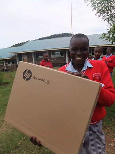 Enoosaen Girls' Secondary pupil proudly brandishes one of the new HP monitors as she helps unload.