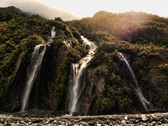 Waterfall (Tim Bow Photography) Tags: world travel newzealand cloud sun sunlight mist mountains color colour green nature water weather rock waterfall glare sub backpacking british welsh moment capture franzjosef hdr clearsky svenska psdtuts timboss81 timbowphotography