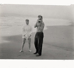 Harry Bowden taking a photograph on the beach, Aug. 1953