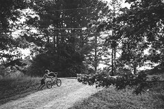 uphill. (Brandy Jaggers) Tags: boy bw sunlight bicycle kids backlight digital fuji naturallight fujifilm manualfocus xe1 rokkor58mmf14 adaptedlens legacyglass minolta5814 fujixe1
