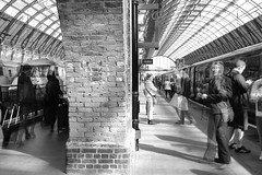 Sitting on the Dock (Mona - B) Tags: trip travel people london monochrome station speed train movement hp time platform potter railway stranger passenger kingscross quais