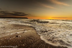 Beach Sunset (Gareth Paskell) Tags: blue sunset sea orange color colour beach yellow clouds landscape movement sand rocks warm tide penbryn