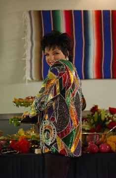 Lucille Austero, played by Liza Minelli, wearing a sparkly top and standing next to a buffet smiling
