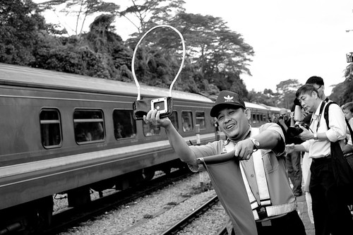 Mr Atan offering the token to incoming train