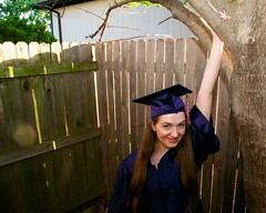 (heatherbirdtx) Tags: portrait woman sunlight tree home girl smile goofy female fence backyard natural expression flash young graduation mortarboard cap flare hanging reach graduate gown milestone favoritespot
