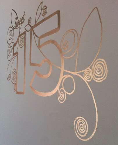 white wall with a gold sweet 15 painted on it