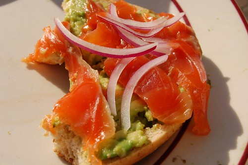 gravlax on a bagel with avocado and red onions