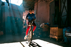 Marrakech (TGKW) Tags: street travel blue light boy shadow red portrait people sun sunlight bicycle cycling kid child market top candid morocco marrakech trousers shafts souq beams 2828