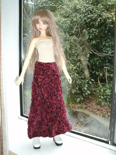 a doll wears a chunky knit skirt