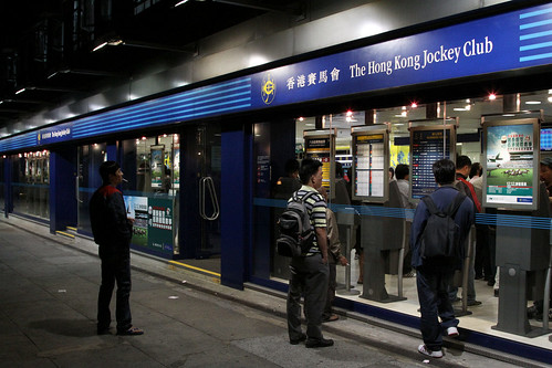 Smokers looking through the window of a Hong Kong Jockey Club store