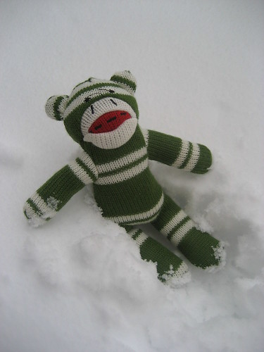 Sock monkey plays in the snow
