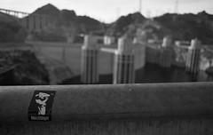 Raise your skinny fists like antenna to heaven (QsySue) Tags: blackandwhite slr graffiti sticker desert dam nevada efke50 wideangle 35mmfilm hooverdam lakemead slap railing canonae1program proletariat developedathome 28mm128 35mmfilmcamera titleisamogwaialbumname