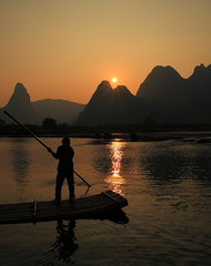 Boatman at sunset (deus77 [busy]) Tags: china sunset panorama sun mountains reflection silhouette reflections river landscape yulong boat guilin yangshuo silhouettes peak  peaks karst boatman  guangxi    flickraward  platinumheartaward internationalgeographic  thepowerofnow flickraward5