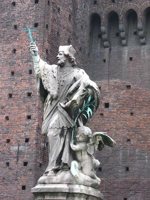 十字架を持った人物と天使の像のフリー写真素材