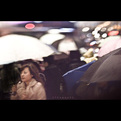 141/365 Strangers (brandonhuang) Tags: street light people woman motion girl rain umbrella lens dof bokeh candid crowd free rainy umbrellas raining lensing brandonhuang freelens freelensing