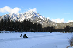 Skating on the Frozen Bow River (zeesstof) Tags: trees mountain snow canada river skaters alberta banff bowriver conifers perambulator banffnationalpark frozenriver canon7d canon18135is zeesstof mountnorwquay alternativebabytransportation