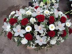 rouwwerk met rode rozen en orchideeën