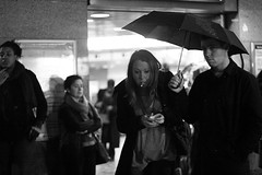 (Che-burashka) Tags: street blackandwhite bw woman man london rain night umbrella 50mm couple cigarette tube entrance bn smoking rainy surprise islington londonist