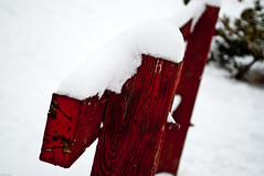 close up of a bright red wooden fence with bright white snow on top