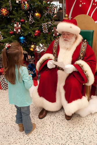 A young girl presents her letter to Santa