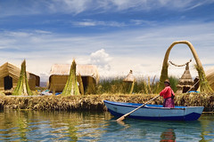The Daily Commute { Explore } (pantha29) Tags: sky woman lake colour peru laketiticaca water reeds boat saturated arch straw vivid floating olympus commute andes oar blueskies polarizer waterside e510 manmadeisland 1260mm andeanculture