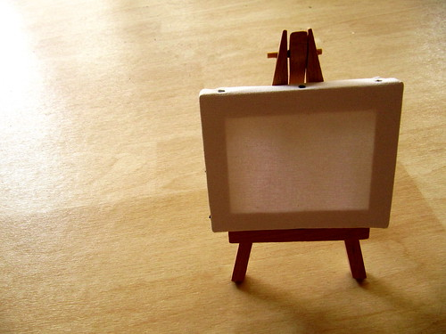 A photo of a blank canvas resting on a small wooden easel. The easel stands alone in a brightly lit room.