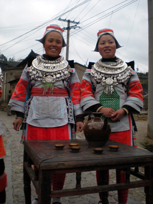 Two girls in bright costumes standing a tea table