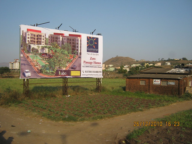 Hoarding of Gulmohar County - 1 BHK & 2 BHK Flats at Talegaon Pune 411 506 - Mahavir Natura, almost Ready for Possession 1 BHK & 2 BHK Flats at Talegaon MIDC Junction on Old Mumbai Pune Highway (NH4) at Vadgaon Maval, Pune 412 106
