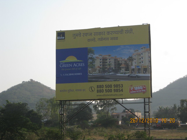 Hoarding of Elite Green Acres - 1 BHK, 1.5 BHK, 2 BHK Flats at Kanhe Phata  - Mahavir Natura, almost Ready for Possession 1 BHK & 2 BHK Flats at Talegaon MIDC Junction on Old Mumbai Pune Highway (NH4) at Vadgaon Maval, Pune 412 106