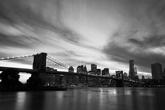 New York, New York. (Vitaliy P.) Tags: new york city nyc bridge sunset sky bw white black building water monochrome brooklyn clouds buildings reflections river lights evening still nikon long exposure downtown angle state dusk manhattan wide dumbo dramatic september east empire gothamist tribute 11th eleven 2010 currents eleventh d80 18135mm vitaliyp