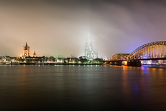 The Cologne Connection (Allard One) Tags: city longexposure nightphotography bridge panorama mist misty fog skyline architecture night river germany deutschland nikon cathedral dom january cologne panoramic le brug riverbank rhine rhein koln nordrheinwestfalen stad rijn lightbeams architectuur januari newyearsday happynewyear duitsland kathedraal keulen rivier spoorbrug stmartinschurch northrhinewestphalia 2011 jaarwisseling oever hohenzollernbrcke kennedyufer musicaldome turnoftheyear nieuwjaarsdag hohedomkirchestpeterundmaria waterflowing purpleglow d700 nikond700 nikkor2470mmf28 nikkor2470 nikon2470 nikonfx allardone allard1 noordrijnwestfalen allardschagercom