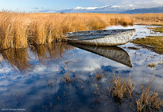 Sunken fishing boat, Aghios Achillios, Prespes, Greece (Christos Andronis) Tags: travel blue winter orange mountain lake water yellow clouds canon reflections landscape pond pastel greece macedonia fishingboat reflexions 24105 prespa   prespes            5dmkii