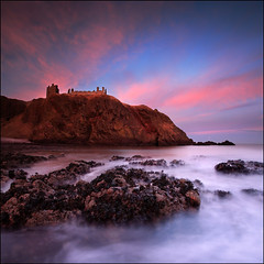 Dunnottar Castle Sunset (angus clyne) Tags: pink blue sunset red sea sky cliff cloud sun moon castle beach wet water stone wall set canon island bay coast scotland weed long exposure aberdeenshire fort angus north shingle rocky fluffy east coastal shore keep inlet loch rise setting inland stronghold dri stoney dunnottar clyne colorphotoaward impressedbeauty vertorama
