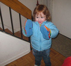 toddler with warm coat and sneakers on her hands