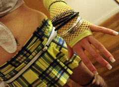 Dani the dancer's playful hand, fishnet glove, and bangles, skirt in blue, acid yellow, and black plaid, navel piercings, white belt, white blouse, French manicure, Wedgwood, Seattle, Washington, USA