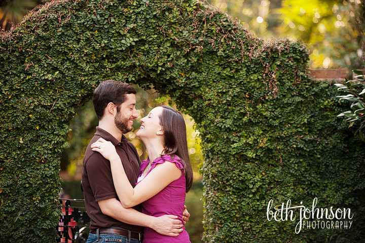 engaged couple in front of ivy covered arch
